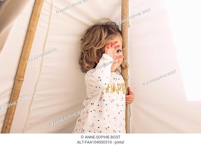 Little girl covering face with hand, smiling shyly