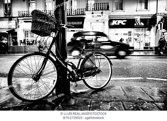 Bicycle with a wicker basket leaning against a lamppost, with a taxi in the background. Piccadilly, London, England