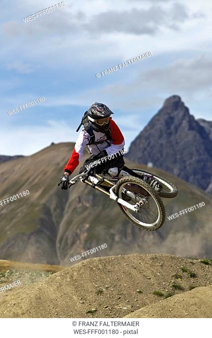 Italy, Livigno, View of man jumping with mountain bike