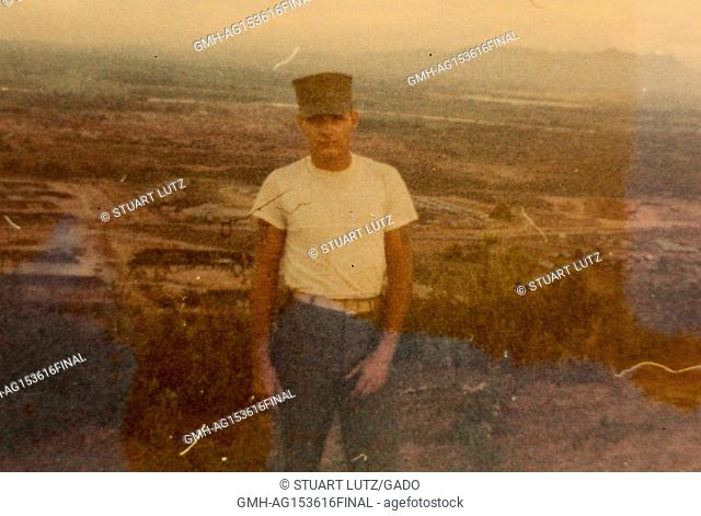 American soldier in Vietnam standing in a field, with a neutral facial expression, wearing a white undershirt and uniform hat, during the Vietnam War, 1968