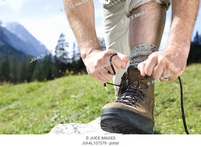 Close-up of man tying shoelaces on hiking boot