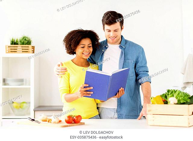happy couple with cooking book at home kitchen