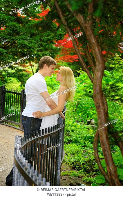 Couple in love leaning on a fence for a path in a park forest