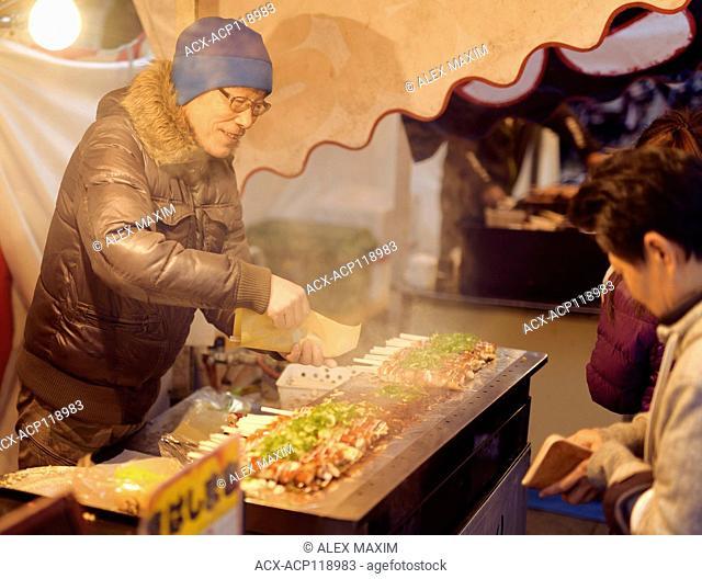 Japanese street food vendor selling Hashimaki, Okonomiyaki rolled on chopsticks, at a street food market in Kyoto, Japan