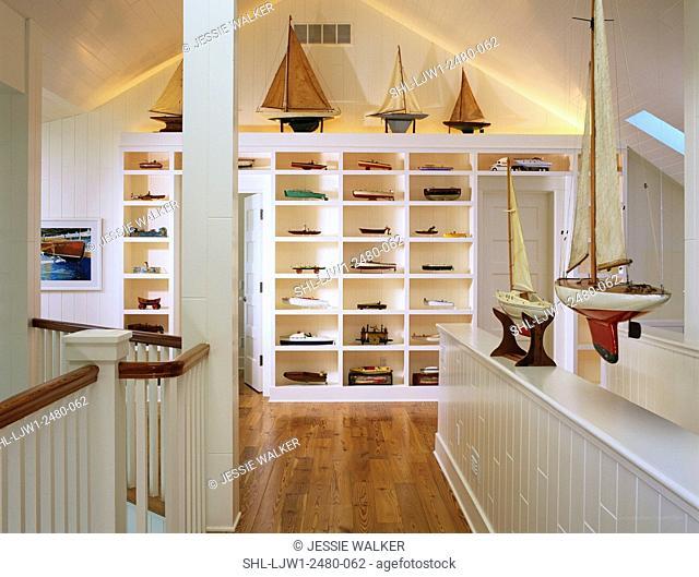 Hallway:Second floor, railing overlooking livingroom, toy boats on display, white walls, wood floor,vaulted ceiling, custom shelving unit