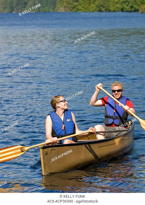 A young couple has fun paddling the famous 'Forest canoe route' near Powell river on the upper Sunshine Coast, Vancouver coast and mountain region