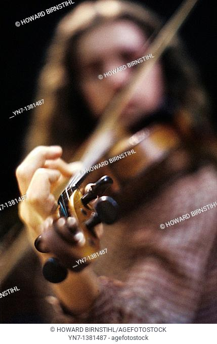 close up shallow focus of a hand forming the notes on a violin with the violinist blurred out in the background