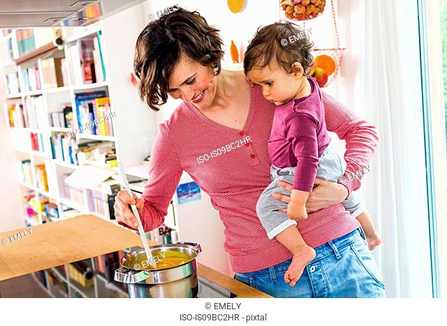Mother holding baby girl in kitchen, whilst stirring pot on stove