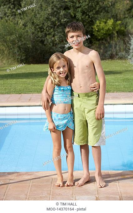 Portrait of sister and brother 6-11 by pool smiling