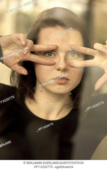 portrait of woman indoors behind glass window, humorous gesture, self-deprecating, self-aware, self-ironic, in Munich, Germany