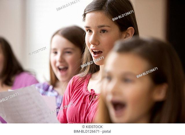 Caucasian girls singing in music class