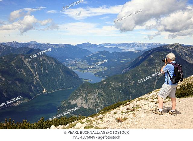 Obertraun, Salzkammergut, Austria, Europe Senior woman photographing the view to Hallstattersee lake from Krippenstein mountain in the Dachstein Massif in the...
