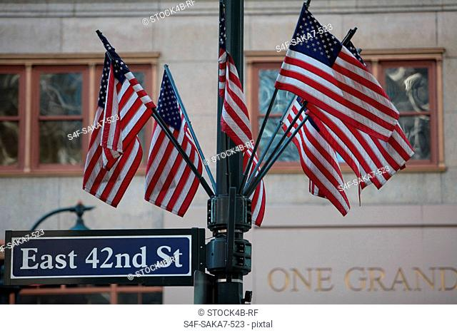 Street name sign with American flags in New York City, USA