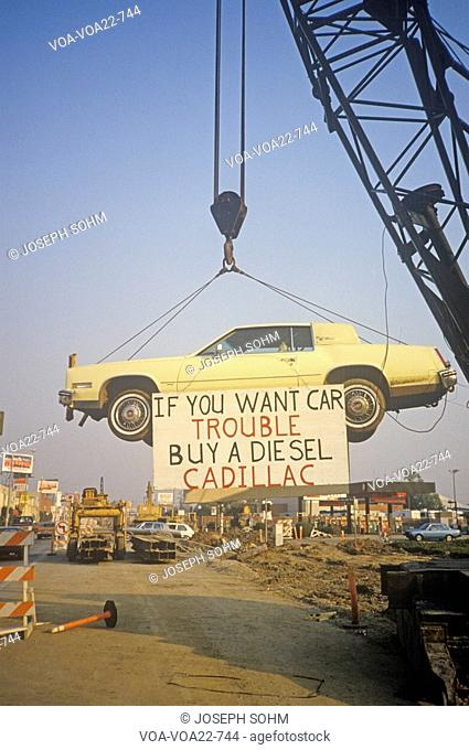 A lemon-yellow Cadillac, which has apparently lived up to its color, hangs from a crane near a service station. A sign warns future car purchasers away from...