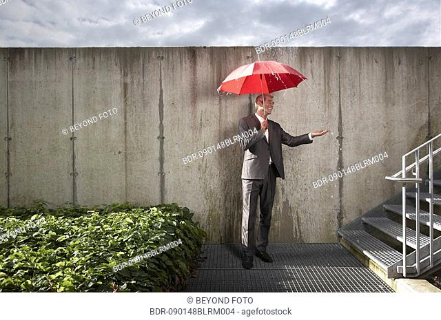 businessman with red umbrella protecting himself from rain