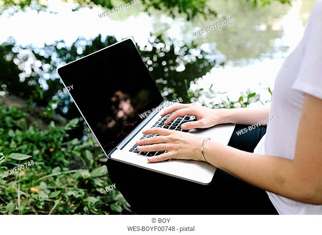 Close-up of woman sitting at lakeside in park using laptop