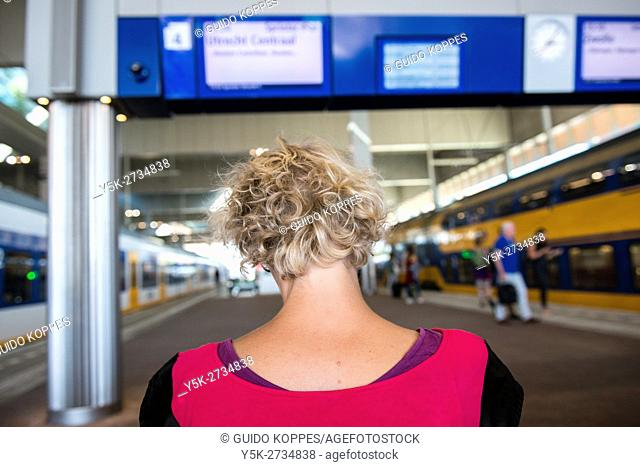 Breda, Netherlands. Blonde, female communter searching for travel information on her smartphone, while waiting on a platform bench for her connecting train...