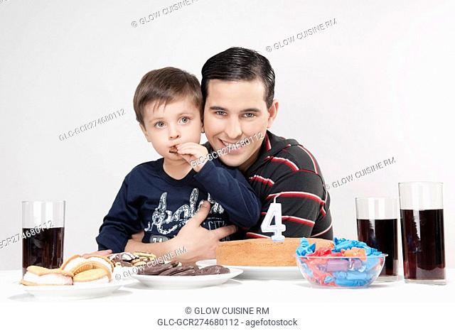Portrait of a man and his son with a birthday cake in front of them