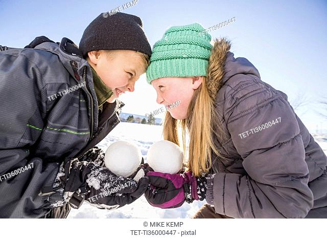 Children (8-9, 10-11) holding snowballs and touching foreheads