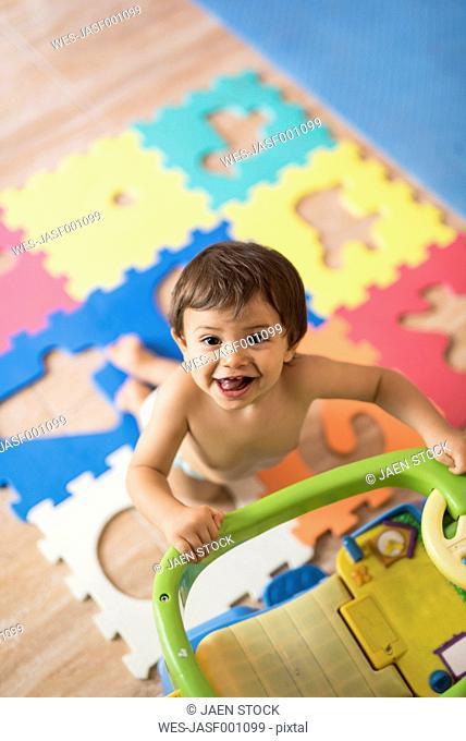 Portrait of baby boy playing in children's room