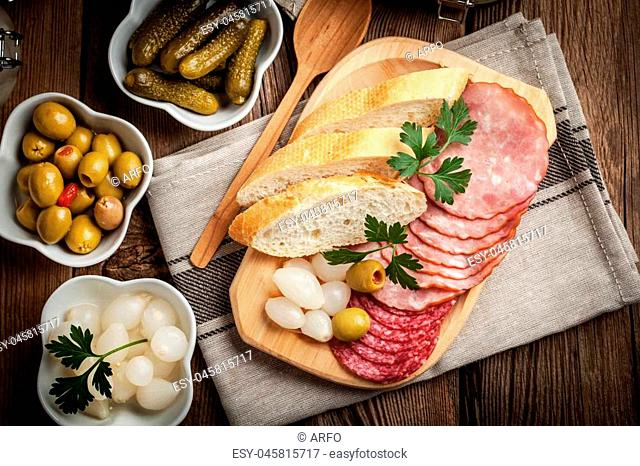Spanish cuisine. Tapas with sliced sausage, salami, olives, marinated onions, cucumber and parsley on a wooden table