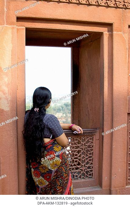 A long hair lady looking outside from the red fort window of Agra ; Uttar Pradesh ; India