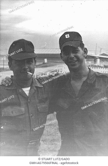 A photograph of two United States Army soldiers posing with their arms around each others shoulders, the serviceman on the left is smoking a cigarette