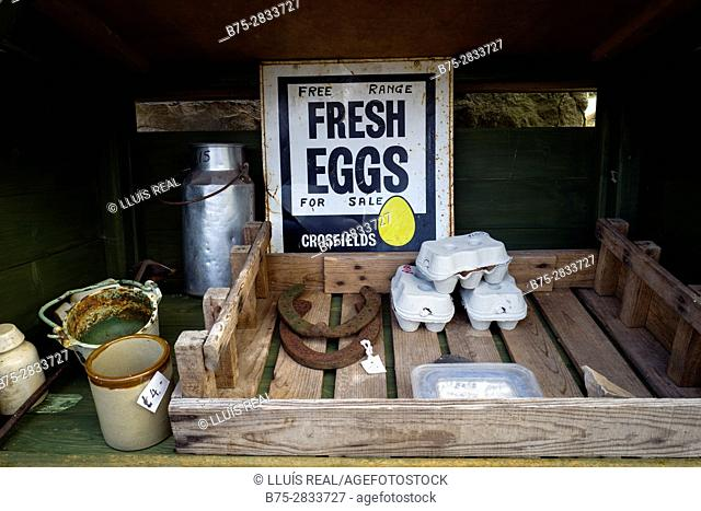 Close-up of a stand selling fresh free-range eggs on a farm, with eggs, two horseshoes and a milk churn.  Gayle, Hawes, North Yorkshire, Yorkshire Dales