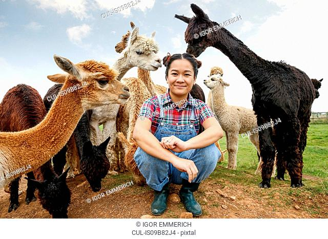 Portrait of woman with alpacas on farm
