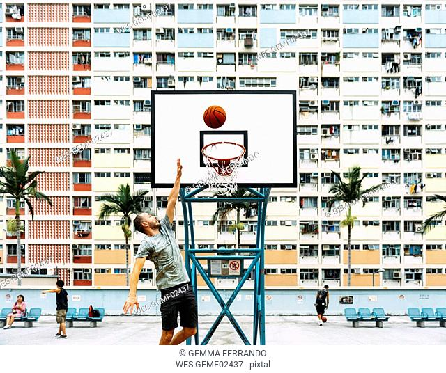 China, Hong Kong, Kowloon, man playing basketball, public housing in the background
