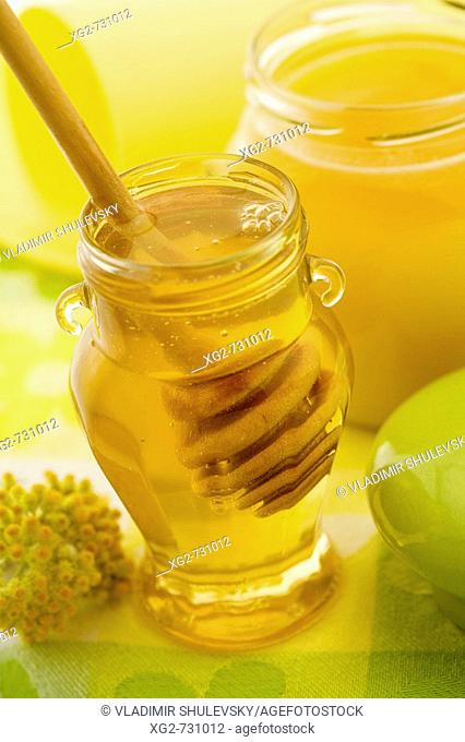 Two jars of honey with dipper