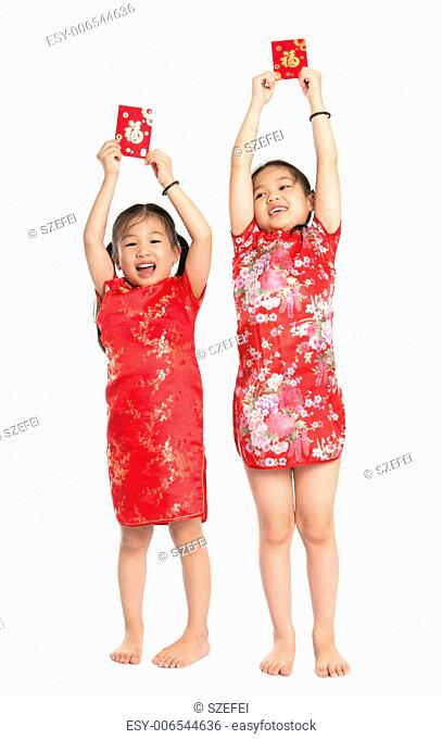 Happy Asian children holding red packet during Chinese New Year, with traditional Cheongsam full length standing isolated on white background