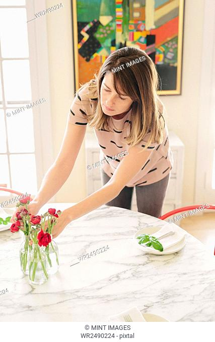A woman arranging fresh cut flowers in the centre of a table
