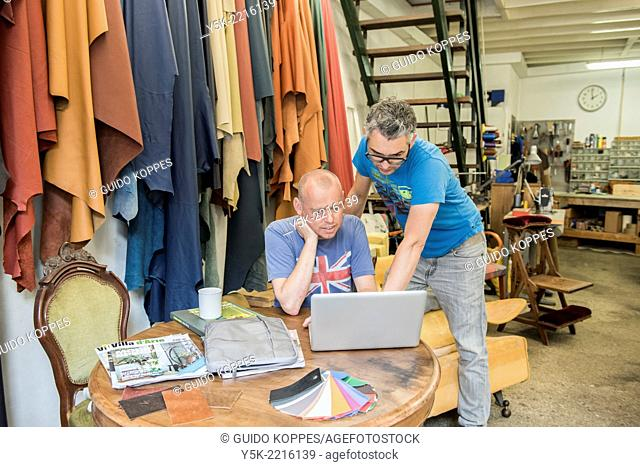 Tilburg, Netherlands. Josef and Werner are apprentice upholsterer and his male partner, both looking at an Apple's notebook, viewing their newly made images