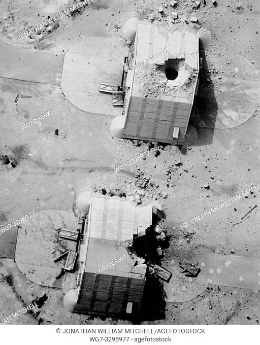 IRAQ -- 11 Mar 1991 -- Two reinforced concrete aircraft hangars at the Ahmed Al Jaber Airfield show the results of a coalition bombing strike during Operation...
