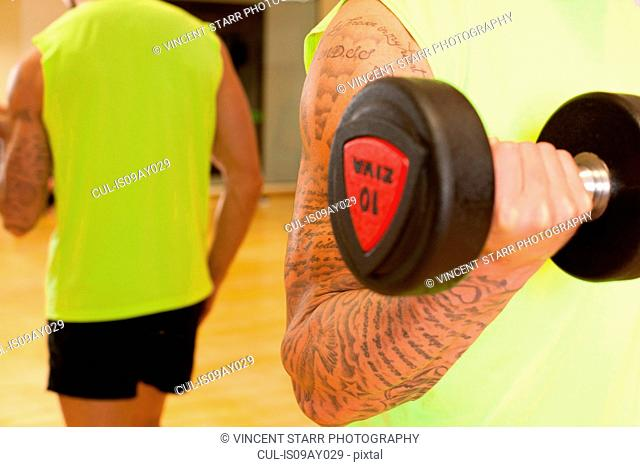 Mirror image of man in gym using dumbbell