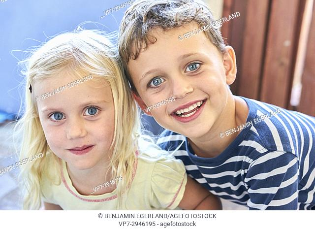portrait of infant siblings putting heads together. Australian ethnicity. During holiday stay in Hersonissos, Crete, Greece