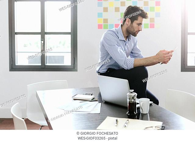 Young businessman working in office, using smartphone