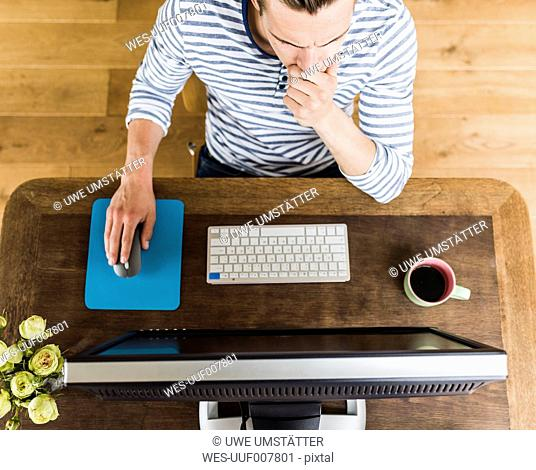Man at wooden desk thinking