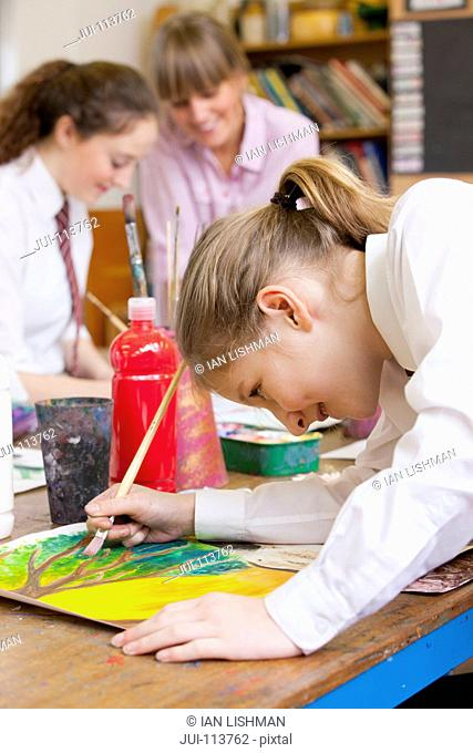 Middle school student painting in art class