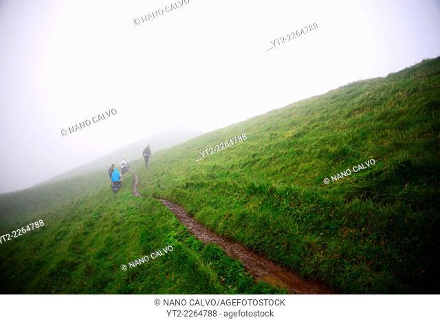 People hiking in foggy Mykines, Faroe Islands