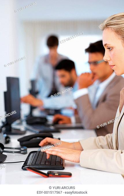 Business woman working on computer with colleagues in background