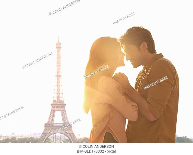 Hispanic couple hugging at Eiffel Tower, Paris, Ile