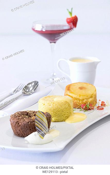 Trio of desserts, including chocolate brownie, sponge pudding and queen of puddings and custard