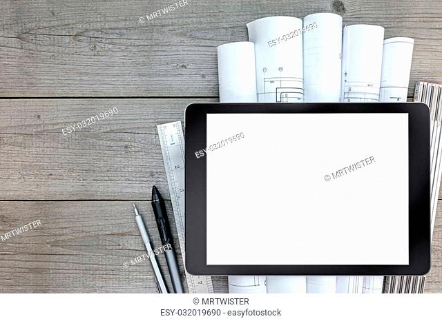 tablet with architectural blueprints and measuring tools on wooden table