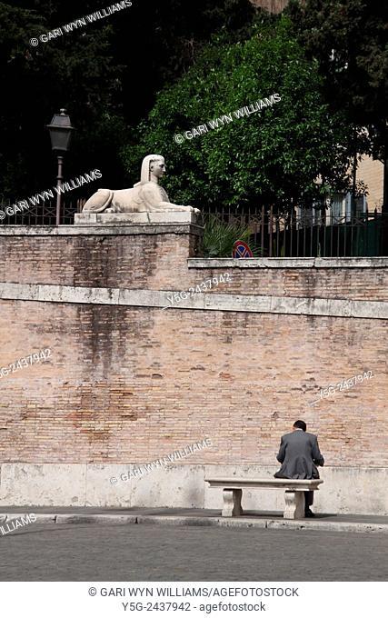 Businessman sitting on bench piazza del popolo square in Rome Italy