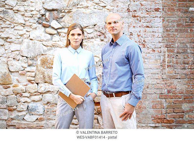 Portrait of two business colleagues at stone wall