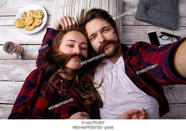 Portrait of young couple lying on the floor taking a selfie