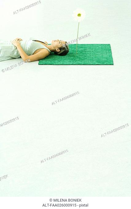 Woman lying on artificial turf next to gerbera daisy, looking up
