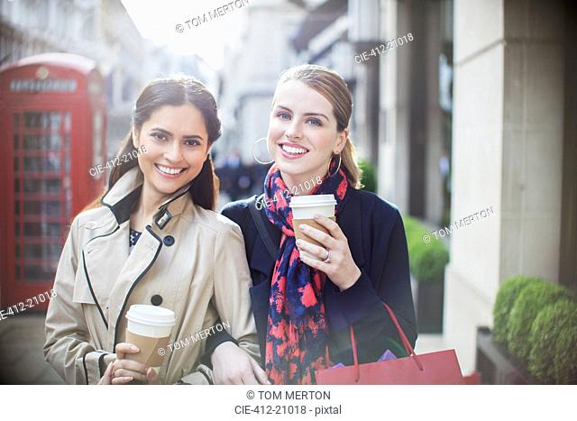 Women drinking coffee together down city street